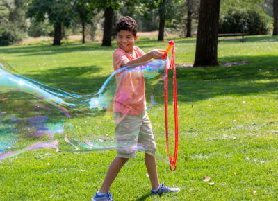 A preteen boy making a huge bubble outside.
