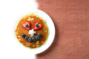 A stack of pancakes with a smilie face made of berries.