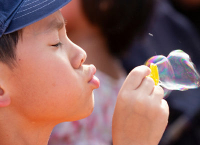 Elementary-aged boy wearing a blue hat faces sideways as he blows a bubble.