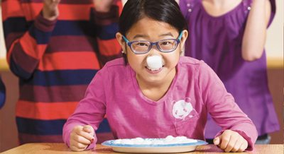 An elementary aged girl with a cotton ball stuck to her nose.