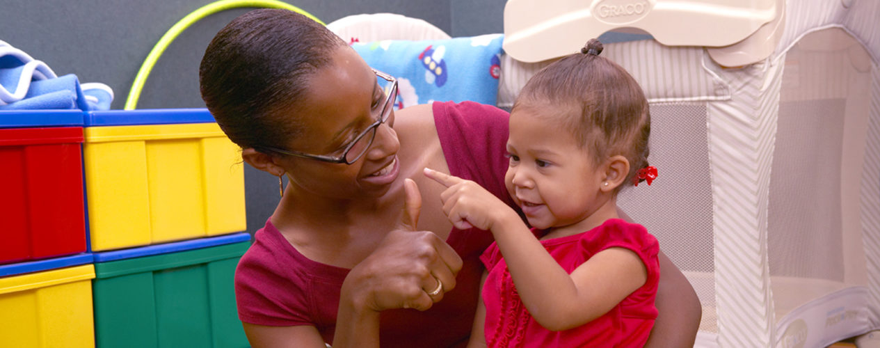 A nursery volunteer does a finger play with a baby.