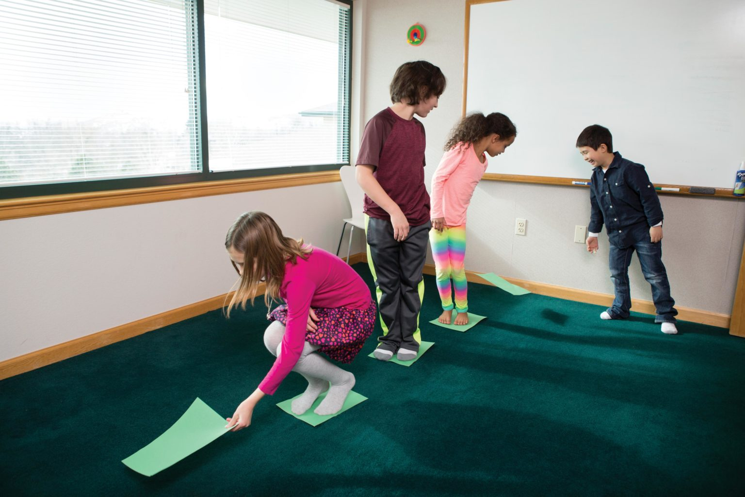 Children in a line, placing green paper on the ground as stepping stones.
