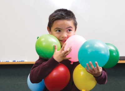 Elementary aged boy trying to hold lots of colorful balloons in his arms.
