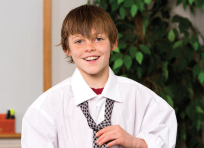 A preteen boy is wearing a large man's dress shirt and is tying a tie around his collar.