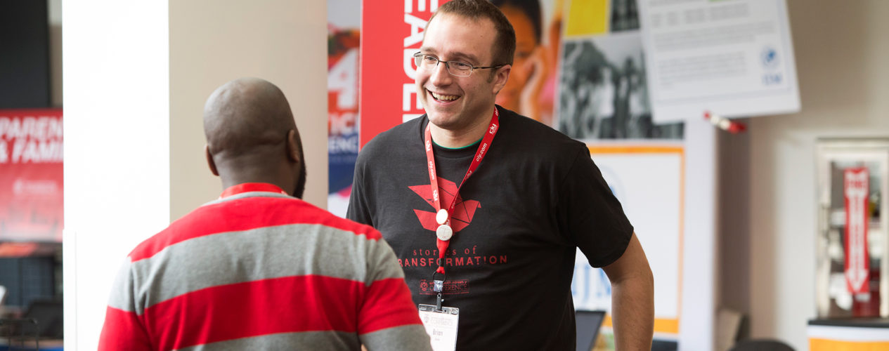 A children's ministry leader at a ministry fair talks to a volunteer.