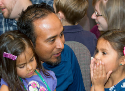 Father sits in a sanctuary with his two daughters and son. One daughter excited has her hands over her mouth.