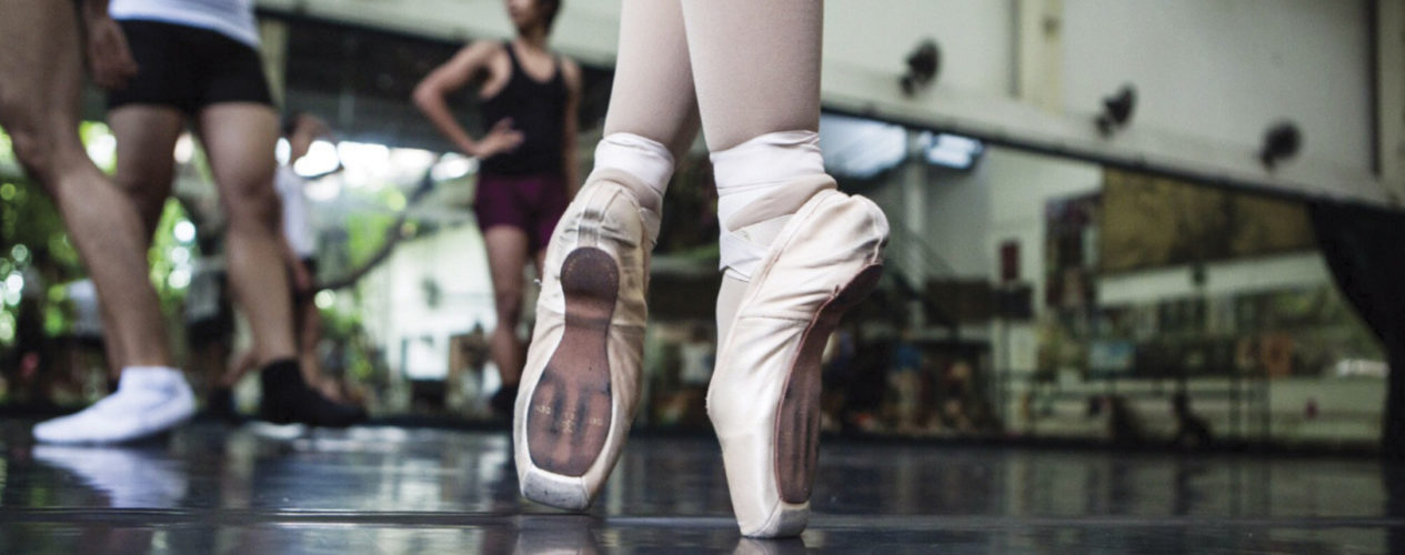 A pair of ballet slippers on point in a studio.
