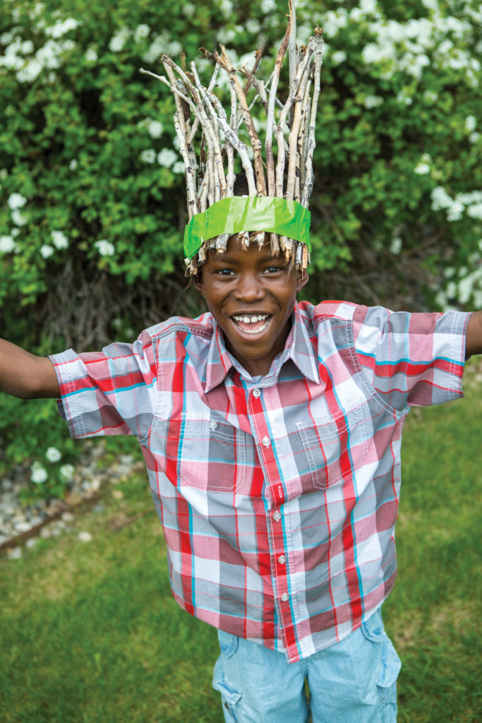 A boy smiling with a crown made of sticks and duct tape.