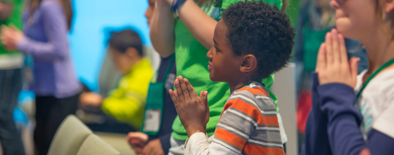 An elementary-aged boy standing in a sanctuary with his hands folded in a time of prayer.