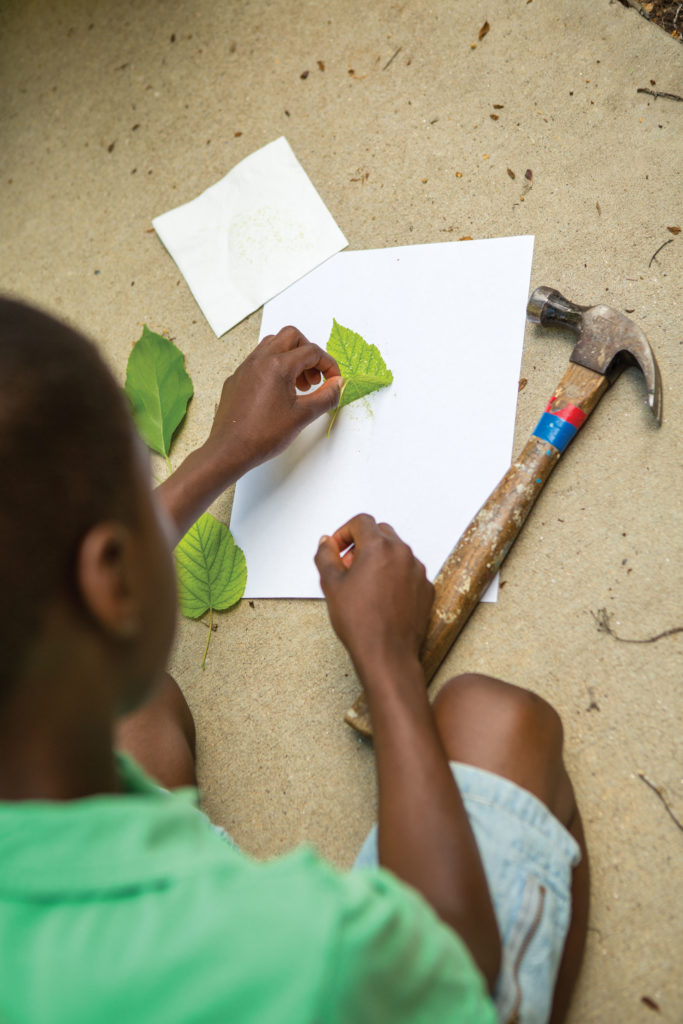 A preteen is making leaf imprints with a hammer.
