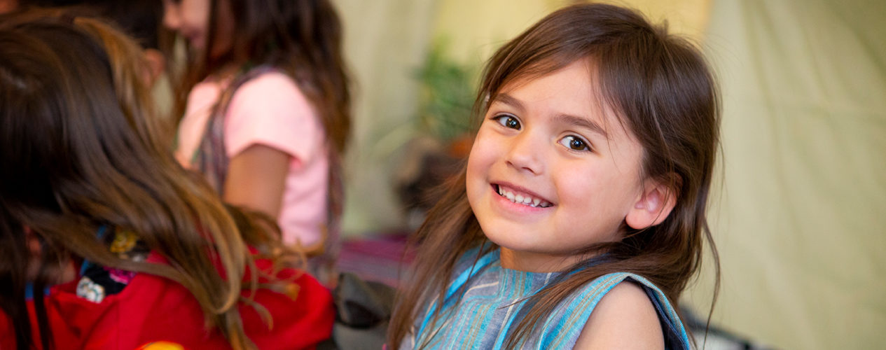 A preschool girl smiles during a lesson on peer pressure.