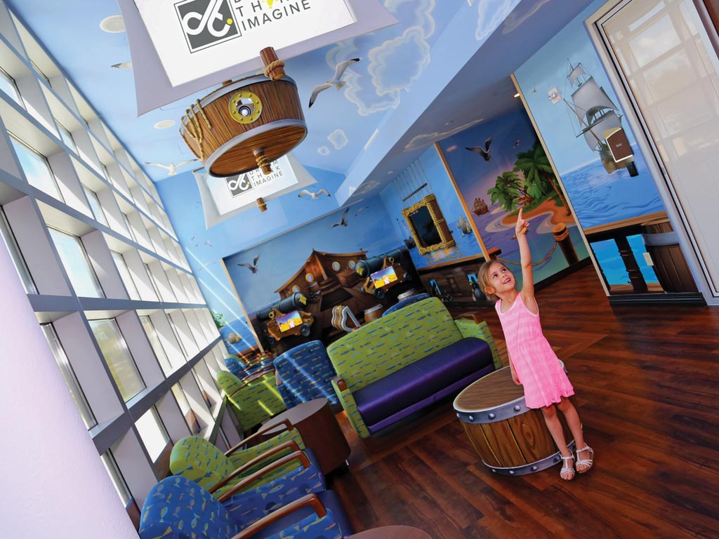 A little girl in a pink dress pointing at the walls of a waiting area. The entire room is decorated with pirate theme, including a crows nest handing from the ceiling.