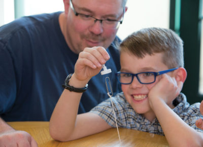 A son is holding a magnet, attracting a paper clip on a string, as his father watches.