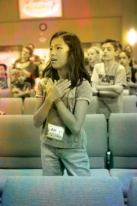 Preteen girl standing with her hands on her heart. She is singing.
