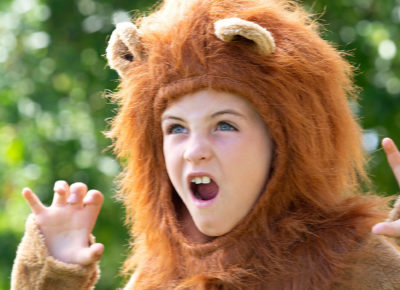 A young girl wearing a lion custom roars with her hands up like claws.