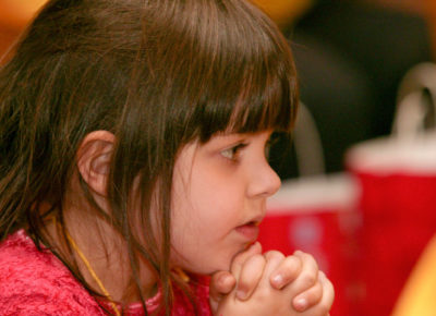 Kindergarten girl prays with her hands by her chin.