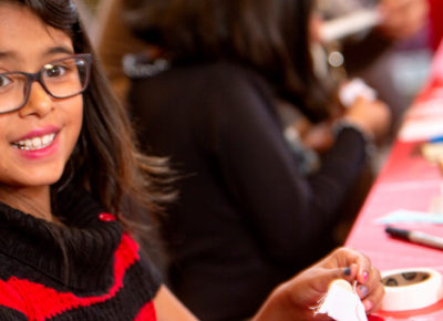 Elementary-aged girl in glasses participates in a craft at a table.