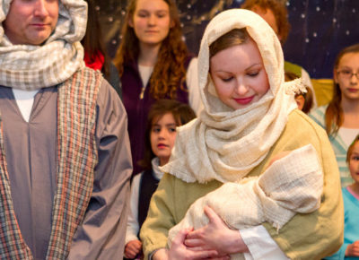 Two adults dressed up as Mary and Joseph are carrying a babydoll. There is a group of kids watching their skit.