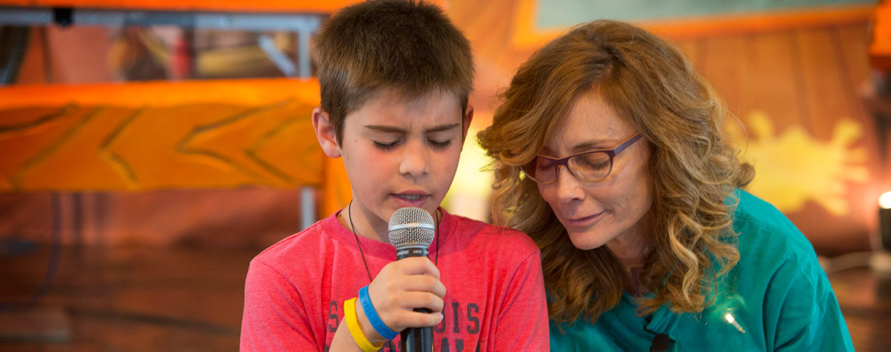A female volunteer and elementary aged boy pray together.