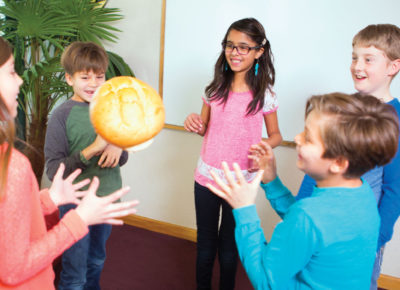 Five preteen children standing in a circle tossing around a mid-sized loaf of bread.