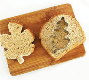 A piece of toast sitting on a cutting board. There's one piece of toast cut into the shape of a leaf, with a whole slice of bread next to it with a cutter on top.