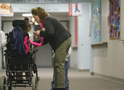 A mom stands in a hallway of a church helping her daughter who is in a wheel chair. Her son is standing next to her, as well.