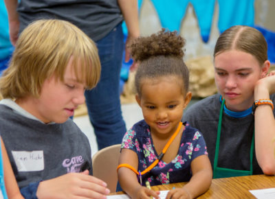 Two volunteers help a group of early elementary children with a craft.