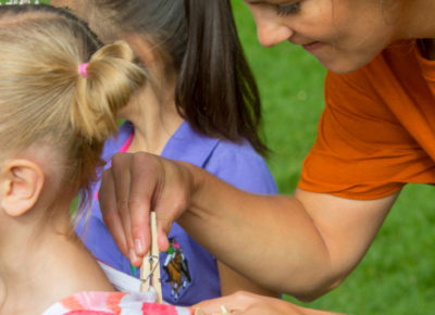 A female volunteer clips a clothespin on an elementary girl as she gets ready to play clothespin tag.