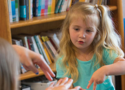 A female volunteer helps teach a preschool girl the Noah Ark finger play from this list of Bible activities. They are in front of a book case in a preschool children's ministry room.