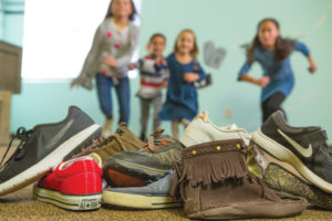 A pile of shoes with children running towards the pile.