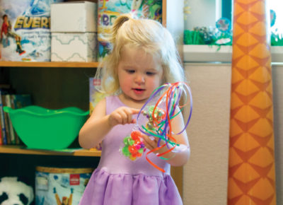 A toddler girl wearing a light purple dress is holding a celebration shaker in her hands.