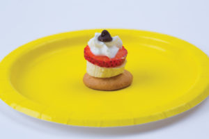 An image of the vanilla wafer banana snack from the Love-Based preschool activities list. It is sitting on a yellow plate.