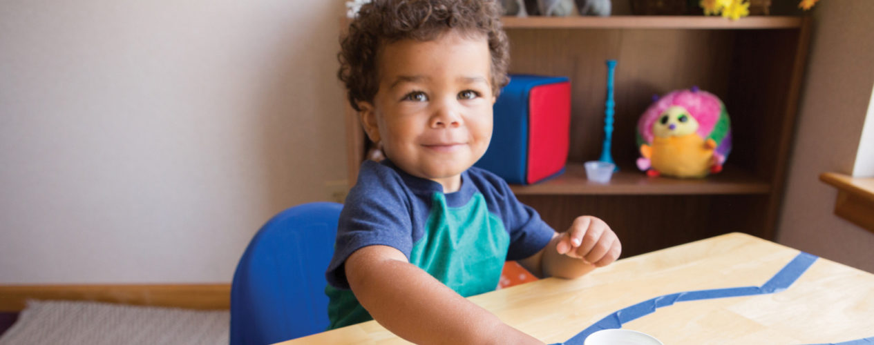 A boy in his nursery classroom participating in the Moses basket idea from this article.