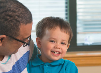 A male volunteer holds a smiling toddler.