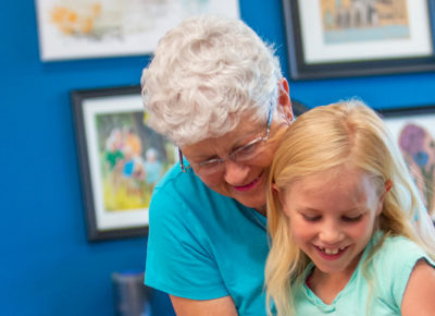 An older woman and a child work together on a cross-generational lesson.