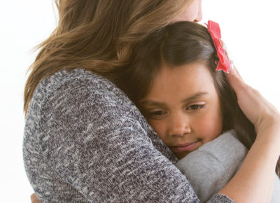 A woman volunteer embraces and elementary aged girl in a large hug.