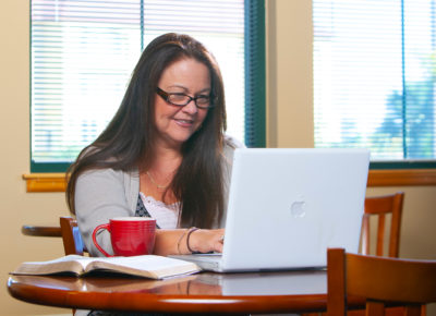 woman with the bible open while using her laptop