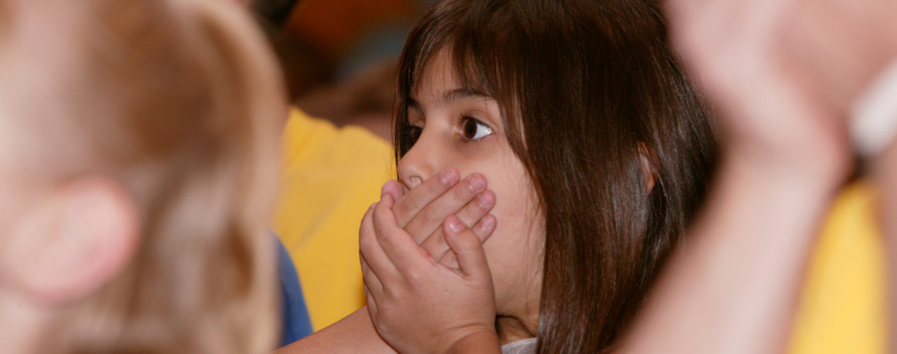 girl in group covering her mouth with her hands
