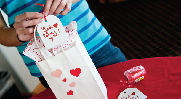 A Valentine's Day goodie bag decorated with a tag that say God loves you!